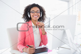 Casual graphic designer working at her desk smiling at camera