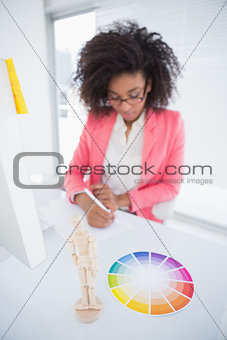Casual graphic designer working at her desk sketching