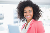 Casual businesswoman smiling at camera holding tablet pc