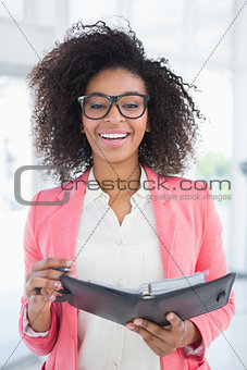 Casual businesswoman holding her diary smiling at camera