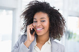 Casual businesswoman talking on phone smiling at camera