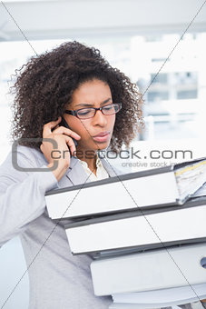 Casual businesswoman talking on phone holding pile of documents