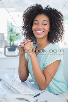 Casual businesswoman smiling at camera at her desk