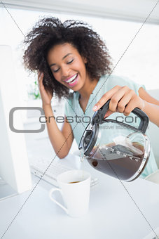 Tired businesswoman pouring a cup of coffee at desk