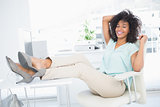 Happy businesswoman sitting with her feet up