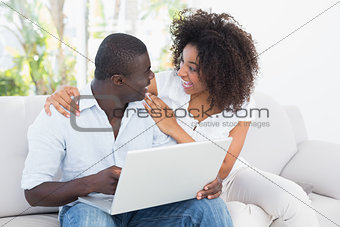Attractive couple using laptop together on sofa