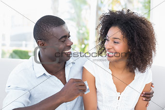 Attractive couple sitting on couch together holding credit card