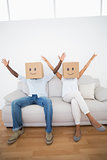 Couple sitting on couch together with boxes over head
