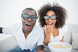 Couple sitting on couch together watching 3d movie
