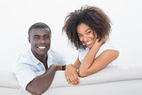 Couple sitting on couch together smiling at camera