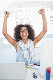Pretty hipster cheering at her desk with laptop