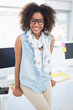 Pretty designer smiling at camera leaning on desk
