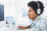 Young designer listening to music as he works