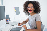 Young pretty designer smiling at camera at her desk