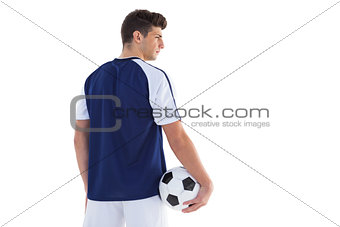 Football player in blue jersey holding ball