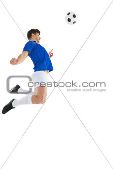 Football player in blue jersey jumping to ball
