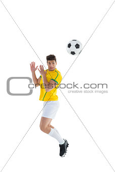 Football player in yellow jersey jumping to ball