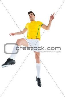 Football player in yellow jersey kicking