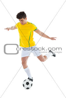 Football player in yellow jersey kicking ball