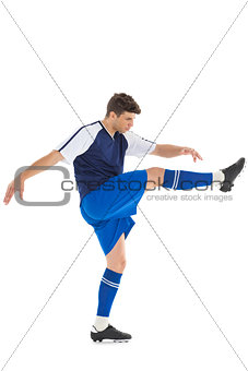 Football player in blue jersey kicking