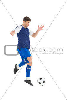 Football player in blue jersey kicking ball