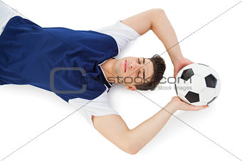 Football player lying on the ground with ball