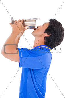 Football player in blue kissing winners cup
