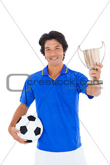 Football player in blue holding winners cup
