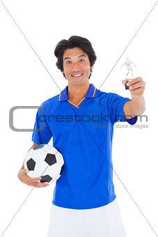 Football player in blue holding winners trophy