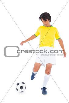 Football player in yellow kicking ball
