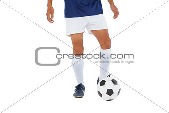 Football player in blue kicking ball