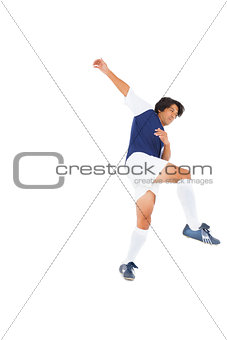 Football player in blue kicking