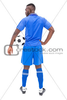 Football player in blue standing with ball