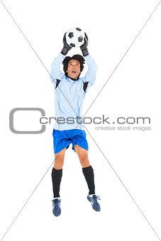 Goalkeeper in blue saving ball