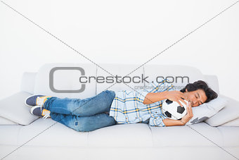Football fan sleeping on couch hugging ball