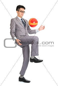 Asian businessman playing soccer
