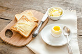 Boiled egg with crispy toasts on the wooden table