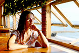 Young woman in cafe near sea