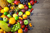 Mix of Fresh Fruits  with water drops on dark wooden table