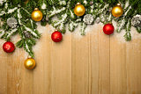 Christmas background with firtree and baubles on wood with snow