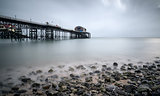 Long exposure landscape of Victorian pier  witn moody sky