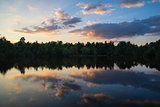 Summer sunset relfected in calm lake landscape