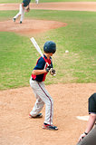 Teen player watching baseball at bat