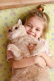 little girl hugging cat lying on a mattress floor