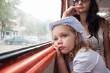 Sad and tired girl looks through window in tram