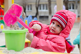 little girl pours sand bucket in sandbox