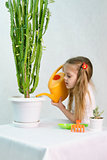 Girl pours from a watering can cacti