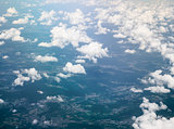 Ground and white fluffy clouds, aerial view from window of airplane