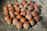 Several hazelnuts on wooden background