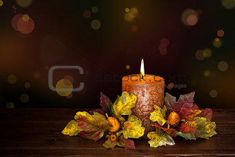Autumn arrangement with candle against defocused holiday lights